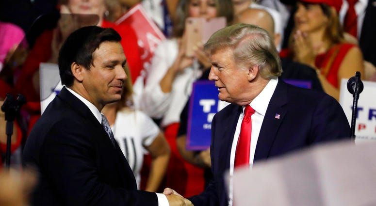 FILE - In this July 31, 2018, file photo, President Donald Trump, right, shakes hands with Florida Republican gubernatorial candidate Ron DeSantis during a rally in Tampa, Fla.(AP Photo/Chris O'Meara, File)