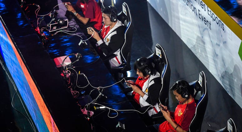 In this Sunday Aug. 26, 2018 photo, the Indonesian team compete in the eSports exhibition at the 18th Asian Games Arena of Valor, Britama Arena, Jakarta. (Dhemas Reviyanto,INASGOC via AP)