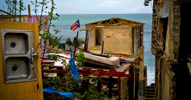 FILE - In this Oct. 5, 2017 file photo, a Puerto Rican national flag is mounted on debris of a damaged home in the aftermath of Hurricane Maria.  (AP Photo/Ramon Espinosa)
