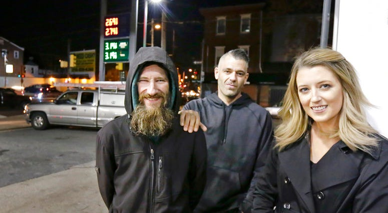 FILE – In this Nov. 17, 2017, file photo, Johnny Bobbitt Jr., left, Kate McClure, right, and McClure's boyfriend Mark D'Amico pose at a Citgo station in Philadelphia. (Elizabeth Robertson/The Philadelphia Inquirer via AP)