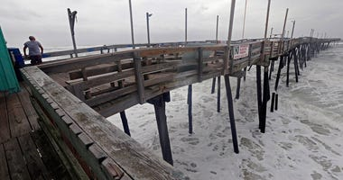 An onlooker checks out the heavy surf at the Avalon Fishing Pier in Kill Devil Hills, N.C., Thursday, Sept. 13, 2018 as Hurricane Florence approaches the east coast. (AP Photo/Gerry Broome)