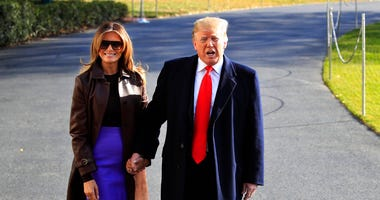 President Donald Trump asks first lady Melania Trump to join him as he concludes talking to reporters on the South Lawn before leaving the White House in Washington, Thursday, Nov. 29, 2018. (AP Photo/Manuel Balce Ceneta)