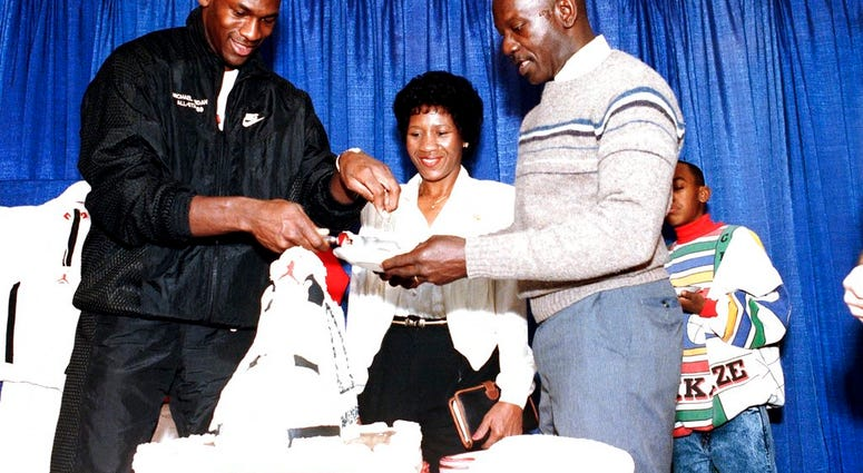 FILE- In this Feb. 17, 1989 file photo, Chicago Bulls' Michael Jordan serves his father, James, a slice of birthday cake as his mother, Doloris, watches during a party in honor of Jordan's 26th birthday in Chicago, Ill. (AP Photo/Charles Bennett, File)