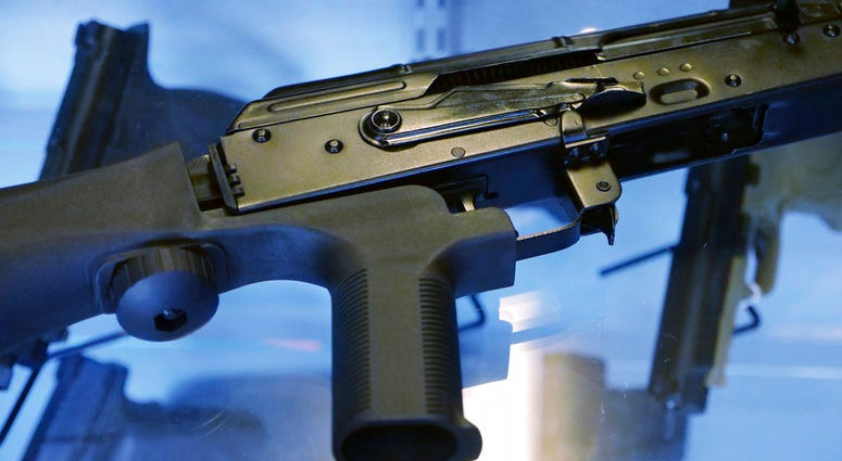 """A little-known device called a """"bump stock"""" is attached to a semi-automatic rifle at the Gun Vault store and shooting range in South Jordan, Utah.  (AP Photo/Rick Bowmer)"""