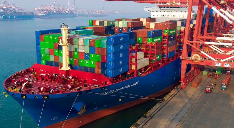 In this Friday, Jan. 11, 2019, photo, workers moor a container ship at a port in Qingdao in east China's Shandong province. (Chinatopix via AP)