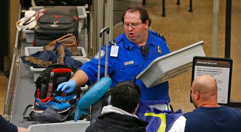 A TSA worker helps passengers at the Salt Lake City International Airport Wednesday Jan., 16, 2019, in Salt Lake City.  (AP Photo/Rick Bowmer)