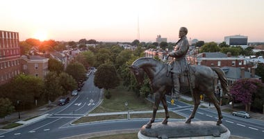 In this July 31, 2017 photo, the sun sets behind the statue of confederate General Robert E. Lee on Monument Avenue in Richmond, Va. (AP Photo/Steve Helber)