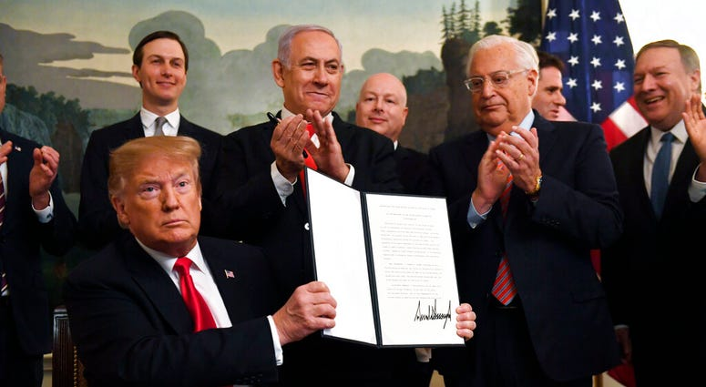 President Donald Trump holds up a signed proclamation recognizing Israel's sovereignty over the Golan Heights. (AP Photo/Susan Walsh)