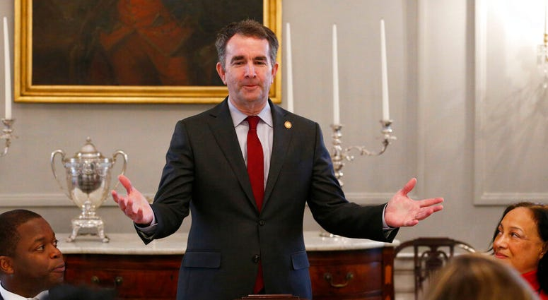 FILE - In this Friday, Feb. 22, 2019 file photo, Gov. Ralph Northam, center, greets members of the Richmond 34 and other African-American leaders for a breakfast at the Governors Mansion at the Capitol in Richmond, Va.  (AP Photo/Steve Helber)