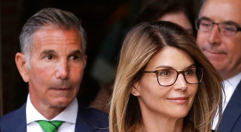 Actress Lori Loughlin, front, and husband, clothing designer Mossimo Giannulli, left, depart federal court in Boston after facing charges in a nationwide college admissions bribery scandal. (AP Photo/Steven Senne, File)