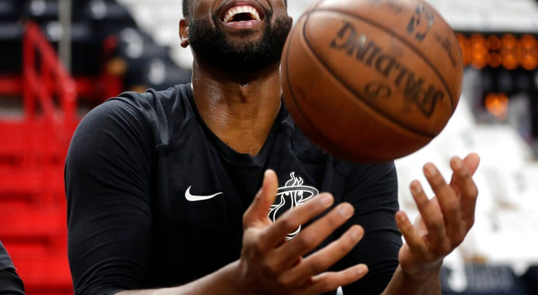 Miami Heat guard Dwyane Wade tosses a basketball before a game against the Philadelphia 76ers, Tuesday, April 9, 2019, in Miami. Wade is playing his final home regular season game before retiring at the end of the season.(AP Photo/Lynne Sladky)