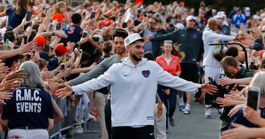 Ty Jerome and other members of the Virginia basketball team are welcomed by fans as they return home after their win of the championship in the Final Four NCAA college basketball tournament. (AP Photo/Steve Helber)