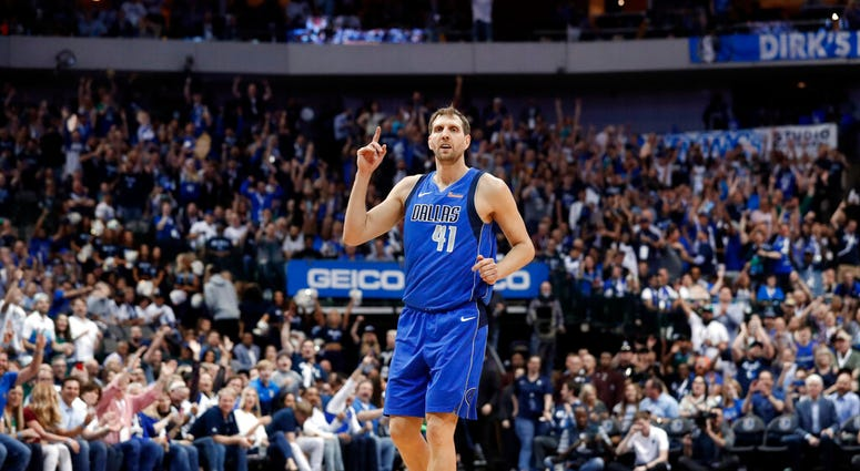 Dallas Mavericks' Dirk Nowitzki (41) celebrates sinking a 3-point basket during the second half of the team's NBA basketball game against the Phoenix Suns in Dallas, Tuesday, April 9, 2019. (AP Photo/Tony Gutierrez)