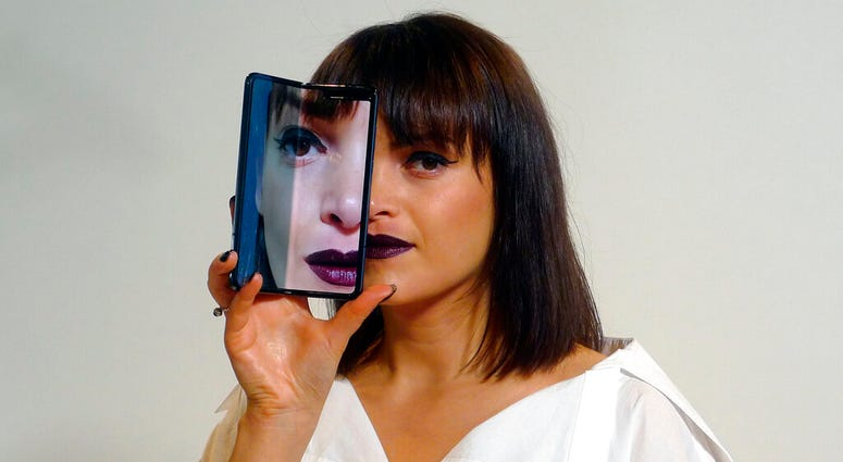 A model holds a Samsung Galaxy Fold smartphone to her face, during a media preview event in London. (AP Photo/Kelvin Chan)