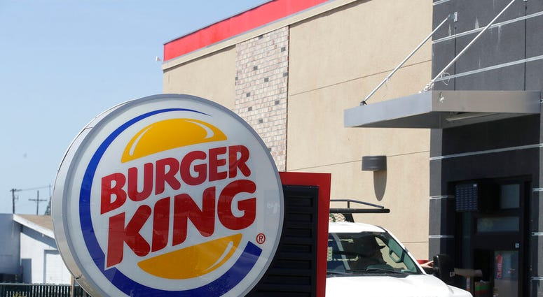 In this Thursday, April 25, 2019, photo a customer takes his order from the drive through window at a Burger King in Redwood City, Calif.  (AP Photo/Jeff Chiu)