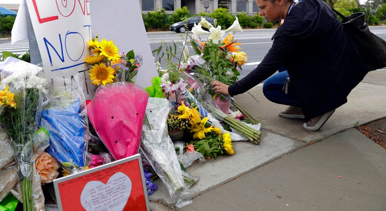A woman leaves flowers on a growing memorial across the street from the Chabad of Poway synagogue in Poway, Calif., on Monday, April 29, 2019. (AP Photo/Greg Bull)
