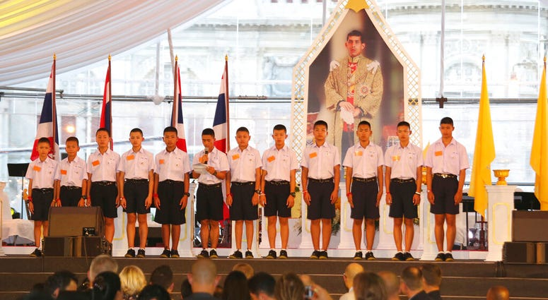 FILE - In this Sept. 6, 2018. file photo, members of the Wild Boars, the soccer team that was rescued from a flooded cave, give thanks in front of Thailand King Maha Vajiralongkorn's image. (AP Photo/Sakchai Lalit, File)