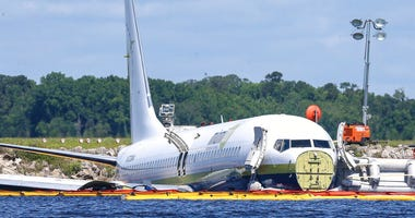 A charter plane carrying 143 people and traveling from Cuba to north Florida sits in a river at the end of a runway, Saturday, May 4, 2019
