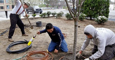 Stephen Faulkner, far left, owner of Faulkner's Landscaping & Nursery, installs an irrigation system alongside workers Gonsalo Garcia, center, and Jalen Murchison, right, at a landscape project in Manchester, N.H. (AP Photo/Elise Amendola)