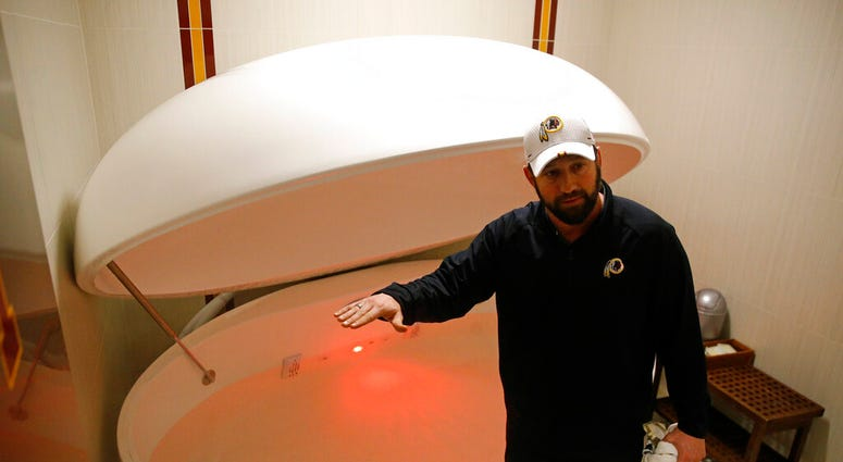 Washington Redskins head athletic trainer Larry Hess demonstrates a salt water float orb inside a recovery room at the team's NFL football training facility in Ashburn, Va. (AP Photo/Patrick Semansky)