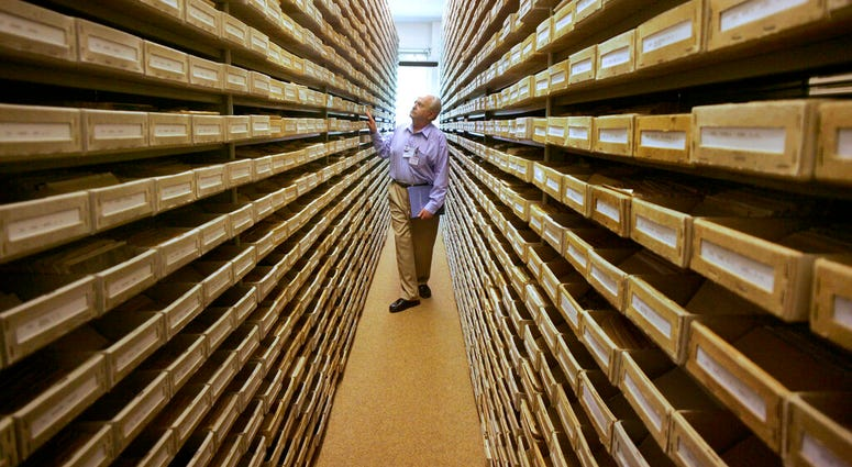 -FILE- In this May 8, 2008 file picture Gary Mokotoff, a Jewish genealogist from New Jersey, takes a look at name registers at the International Tracing Service in Bad Arolsen, central Germany. (AP Photo/Michael Probst, file)