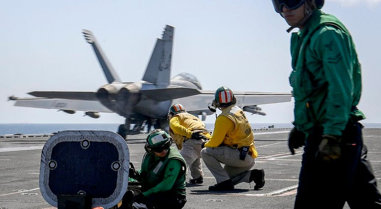 "In this Monday, May 20, 2019 photo, released by U.S. Navy, an F/A-18E Super Hornet from the ""Jolly Rogers"" of Strike Fighter Squadron.  (Mass Communication Specialist 3rd Class Jeff Sherman/U.S. Navy via AP)"