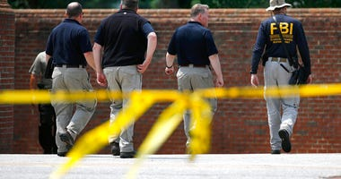The FBI works outside an entrance to a municipal building that was the scene of a shooting,