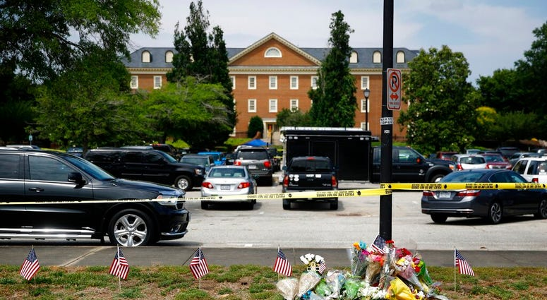 A makeshift memorial rests at the edge of a police cordon in front of a municipal building that was the scene of a shooting, Saturday, June 1, 2019, in Virginia Beach, Va. (AP Photo/Patrick Semansky)