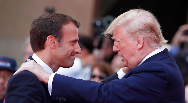 French President Emmanuel Macron, left, meets U.S President Donald Trump during a ceremony to mark the 75th anniversary of D-Day at the Normandy American Cemetery in Colleville-sur-Mer, Normandy, France.  (Ian Langsdon/POOL via AP)