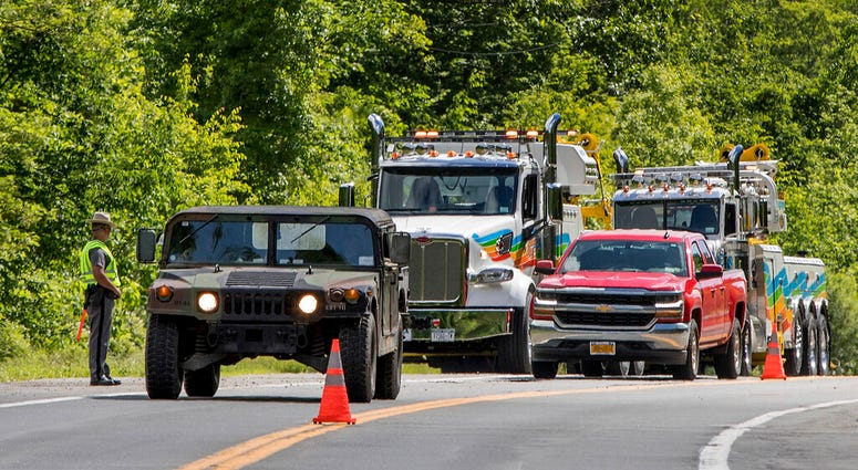 Military police direct traffic along Route 293 near the site where an armored personnel vehicle overturned killing at least one person.  (AP Photo/Allyse Pulliam)