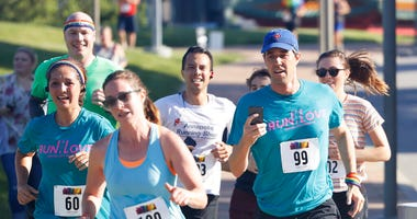 Democratic presidential candidate Beto O'Rourke, right, runs the Capital City Pride Fest Fun Run 5K with his wife Amy, left, Saturday, June 8, 2019, in Des Moines, Iowa. (AP Photo/Charlie Neibergall)