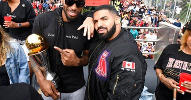 Toronto Raptors forward Kawhi Leonard points at his playoffs MVP trophy as he poses with performing artist Drake during the 2019 Toronto Raptors NBA basketball championship parade. (Frank Gunn/The Canadian Press via AP)