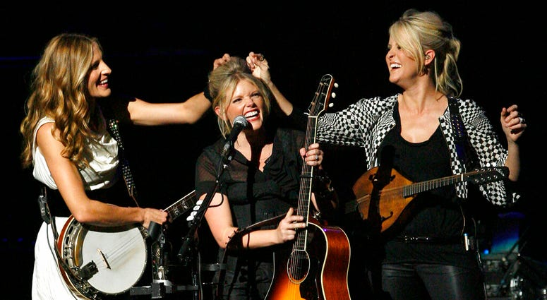 FILE - In this Oct. 18, 2007 file photo, Emily Robison, left, and Martie Maguire, right, adjust Natalie Maines' hair as the Dixie Chicks perform at the new Nokia Theatre in Los Angeles. (AP Photo/Gus Ruelas, file)