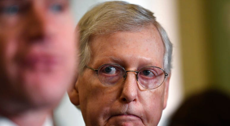 Senate Majority Leader Mitch McConnell of Ky., right, listens as Sen. Todd Young, R-Ind., left, speaks to reporters following the weekly policy luncheon on Capitol Hill in Washington, Tuesday, July 9, 2019. (AP Photo/Susan Walsh)