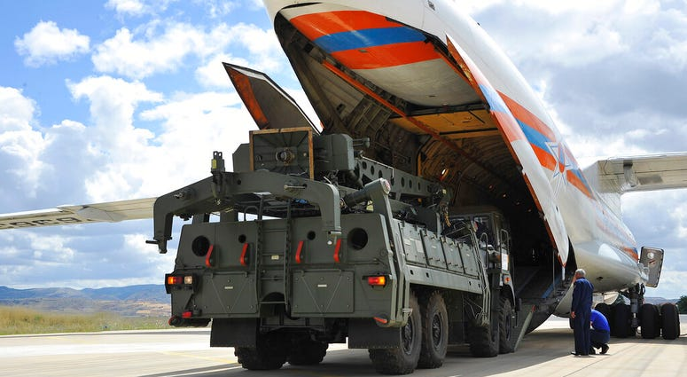 Military vehicles and equipment, parts of the S-400 air defense systems, are unloaded from a Russian transport aircraft, at Murted military airport in Ankara, Turkey. (Turkish Defence Ministry via AP, Pool)