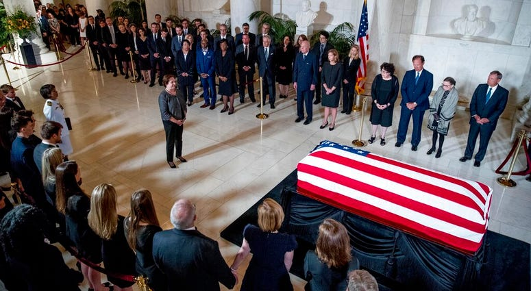 Associate Justice Elena Kagan, center left, speaks at a private ceremony in the Great Hall of the Supreme Court in Washington, Monday, July 22, 2019, where late Supreme Court Justice John Paul Stevens lies in repose. (AP Photo/Andrew Harnik, pool)