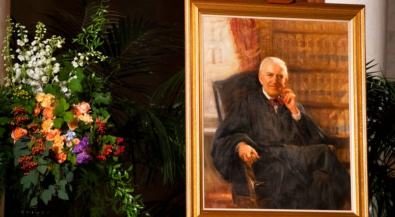 A portrait of the late Supreme Court Justice John Paul Stevens is displayed in the Great Hall of the U.S. Supreme Court, Monday, July 22, 2019, in Washington, as the former justice lies in repose at the court. (AP Photo/Manuel Balce Ceneta)