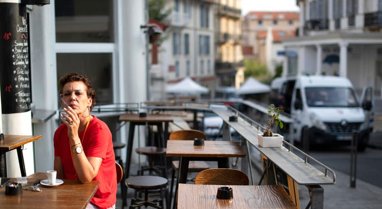 A woman has a cigarette with her morning coffee in Biarritz, France, on the third day of the G-7 summit, Monday, Aug. 26, 2019.  (AP Photo/Peter Dejong)