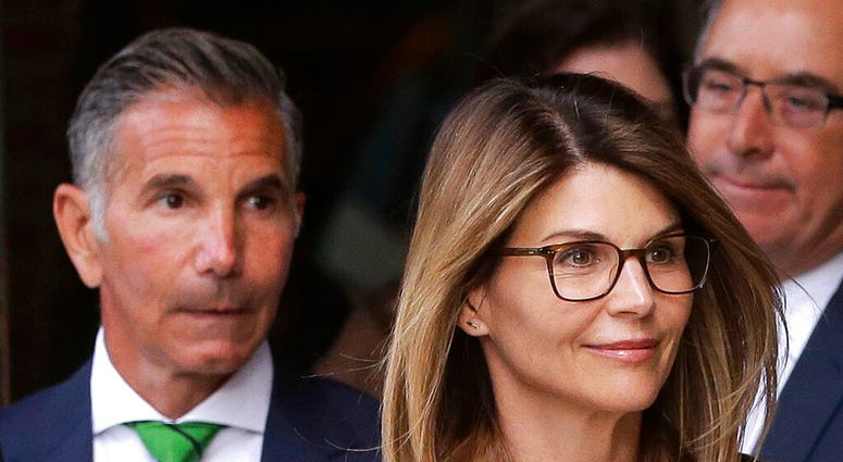 FILE - In this April 3, 2019, file photo, actress Lori Loughlin, front, and husband, clothing designer Mossimo Giannulli, left, leave federal court in Boston after facing charges.   (AP Photo/Steven Senne, File)
