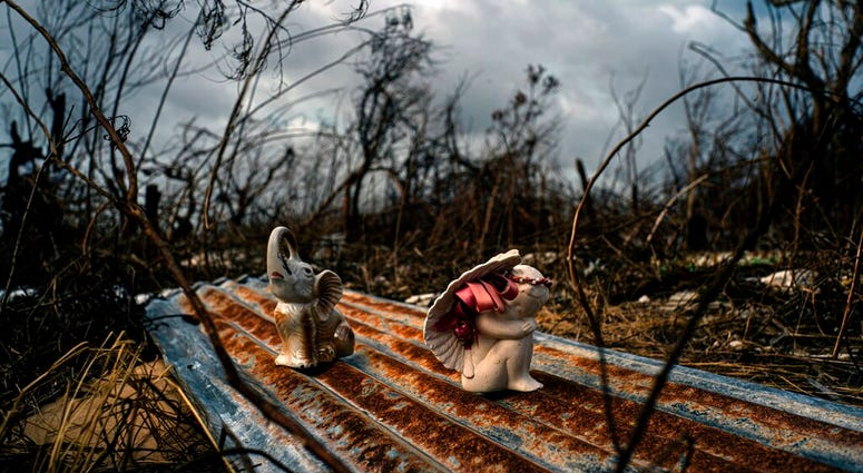 Porcelain figures rest among the remains of a shattered house at the aftermath of Hurricane Dorian in Freetown, Grand Bahama, Bahamas, Friday Sept. 13, 2019.