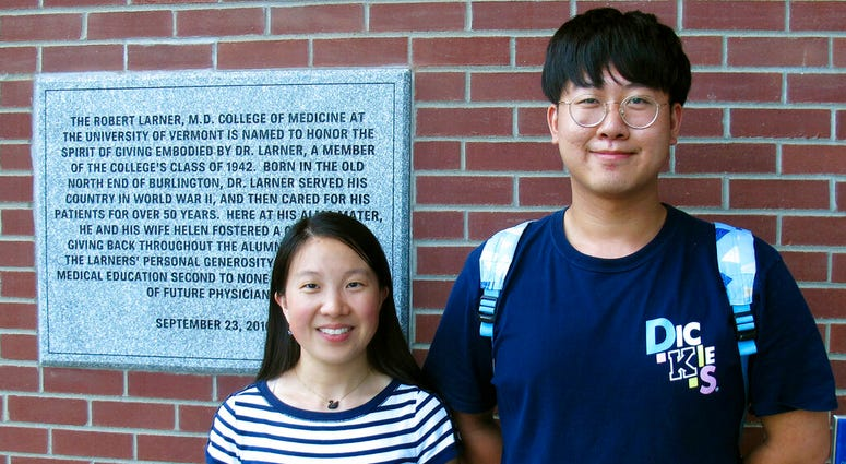 In this photo Aug. 16, 2019, photo, Chinese graduate students Zhaojin Li, left, and Pengfei Liu, pose in front of the entrance to the Robert Larner College of Medicine at the University of Vermont in Burlington, Vt. (AP Photo/Wilson Ring)