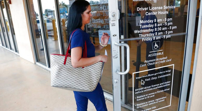 A woman enters a Florida Highway Safety and Motor Vehicles drivers license service center, Tuesday, Oct. 8, 2019, in Hialeah, Fla. (AP Photo/Wilfredo Lee)