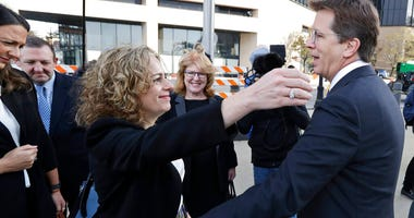 Attorneys Linda Singer and Mark Lanier hug outside the U.S. Federal courthouse, Monday, Oct. 21, 2019, in Cleveland. Both Singer and Lanier are the plaintiffs attorneys.   (AP Photo/Tony Dejak)