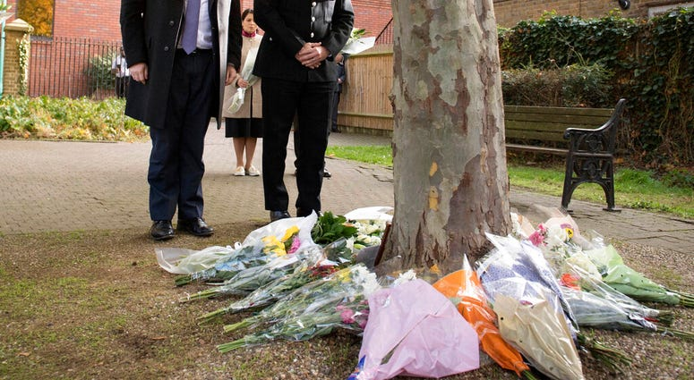 Britain's Prime Minister Boris Johnson stands with the Chief Constable of Essex Police, Ben-Julian Harrington after laying flowers during a visit to Thurrock Council Offices, England. (Stefan Rousseau/Pool via AP)