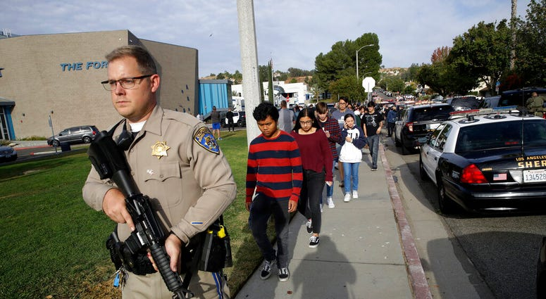This Nov. 14, 2019 file photo shows students being escorted out of Saugus High School after a shooting on the campus in Santa Clarita, Calif. (AP Photo/Marcio Jose Sanchez, File)