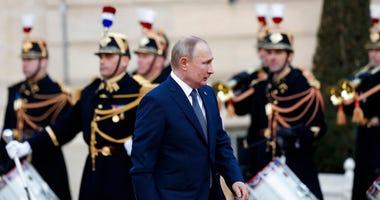 Russian President Vladimir Putin walks past Republican guards as he arrives at the Elysee Palace Monday, Dec. 9, 2019 in Paris. (AP Photo/Thibault Camus)