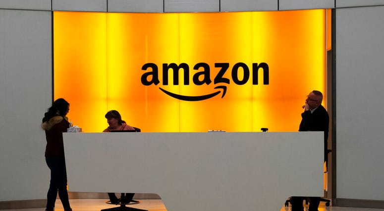 FILE - In this Feb. 14, 2019, file photo people stand in the lobby for Amazon offices in New York. (AP Photo/Mark Lennihan, File)