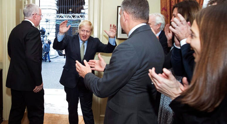 Britain's Prime Minister Boris Johnson is greeted by staff as he returns to 10 Downing Street, London, after meeting Queen Elizabeth II and accepting her invitation to form a new government, Friday Dec. 13, 2019. (Stefan Rousseau/PA via AP)