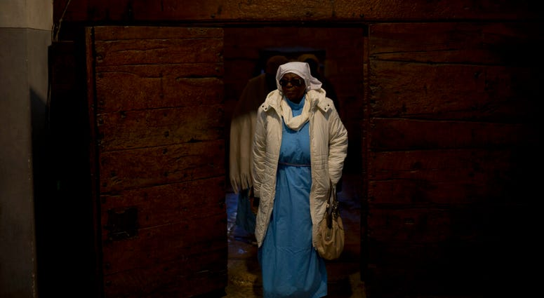A Christian pilgrim from Nigeria enters the Church of the Nativity, built on top of the site where Christians believe Jesus Christ was born, on Christmas Eve in the West Bank City of Bethlehem, Tuesday, Dec. 24, 2019. (AP Photo/Majdi Mohammed)