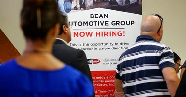 FILE - In this Sept. 18, 2019, file photo people stand in line to inquire about jobs available at the Bean Automotive Group during a job fair in Miami. On Friday, Jan. 10, 2020, the U.S. government issues the December jobs report. (